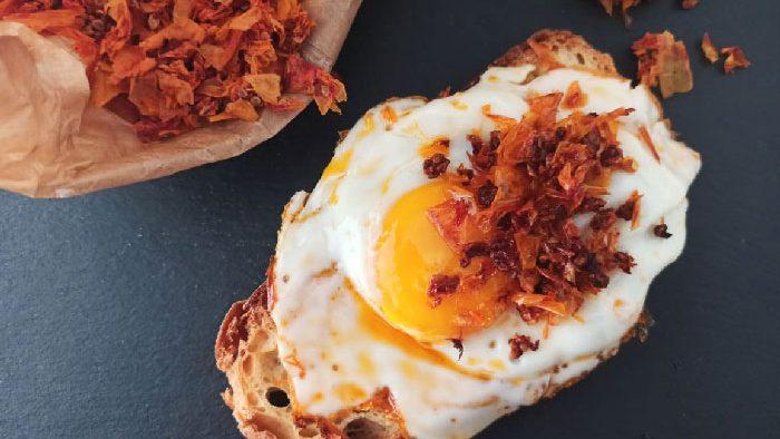 uovo fritto con bucce di pomodoro